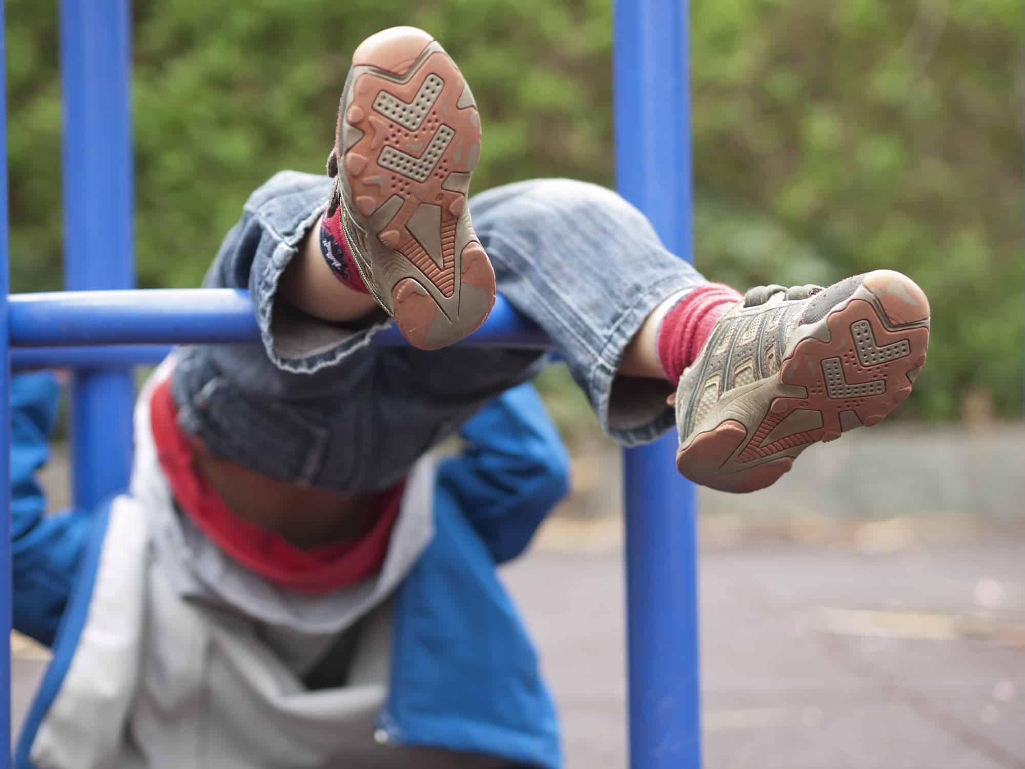 Child Hanging Upside Down In Climbing Frame Of A Playground. Focus On Feet With Shoes Only. Parts Of Climbing Frame Visible.